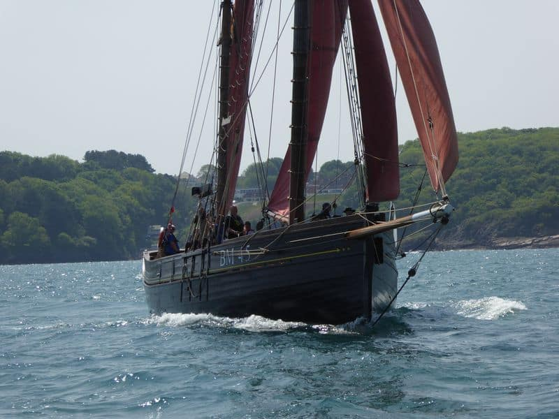 Pilgrim ploughs through the water under full sail.