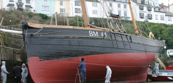 Antifouling the hull of Pilgrim in Brixham.