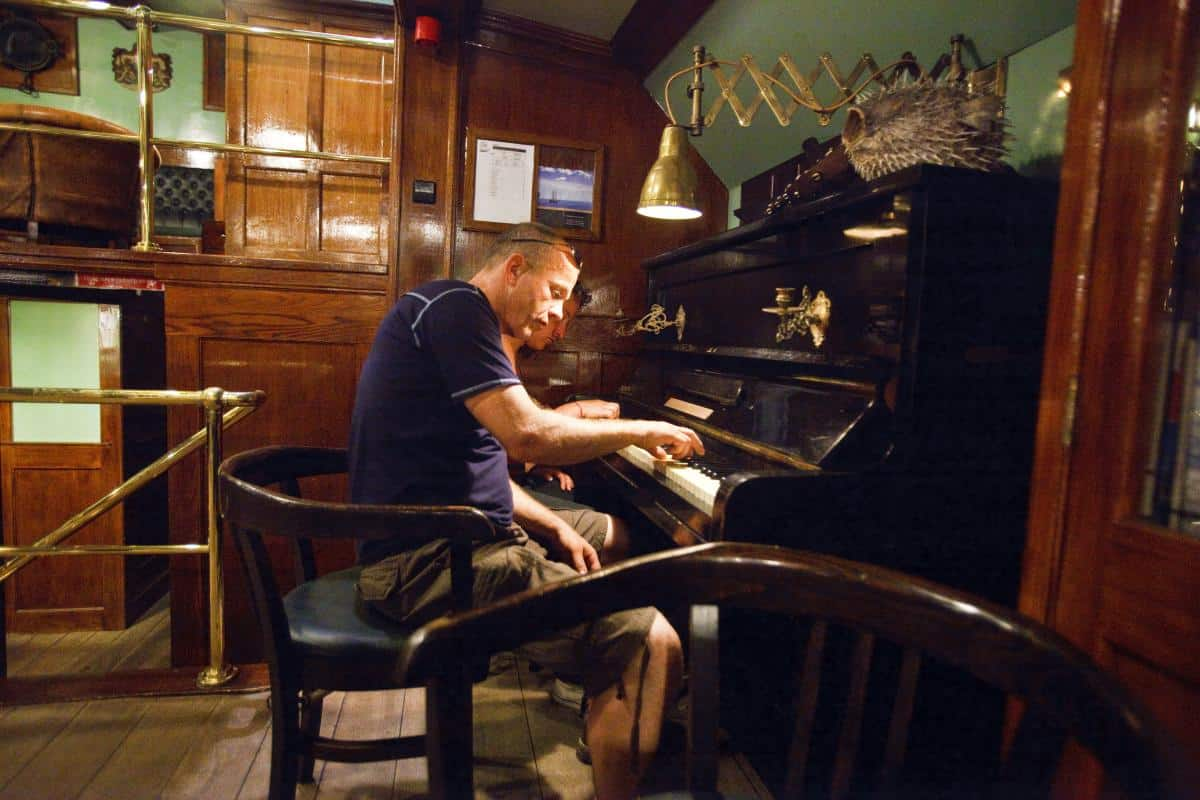 Guests playing the piano in Oosterschelde's saloon