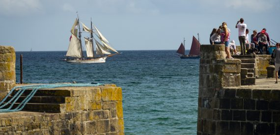 Anny sailing off a historic harbour in the West Country