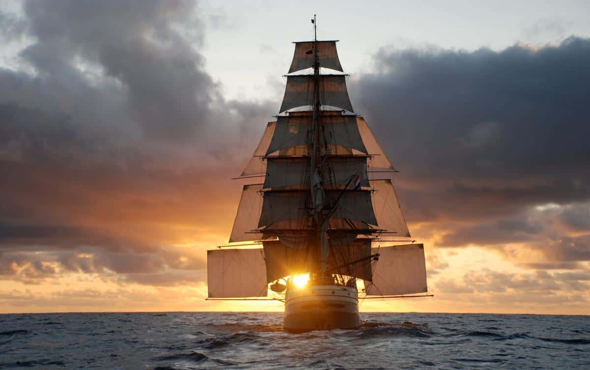 square rigger in the sunset with stunsails
